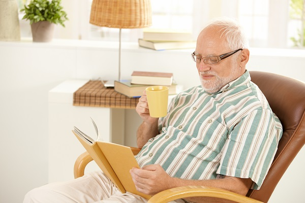 Elderly man sitting in chair smiling at book.